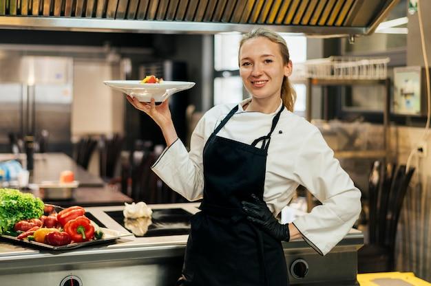 Smiley vrouwelijke chef-kok met schotel in haar hand