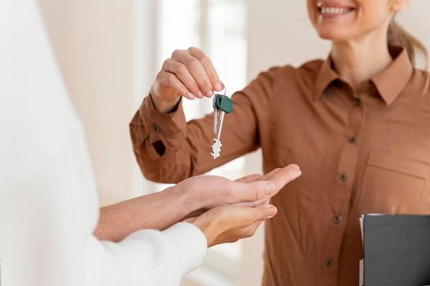Smiley vrouwelijke makelaar overhandigen paar de sleutels voor hun nieuwe huis