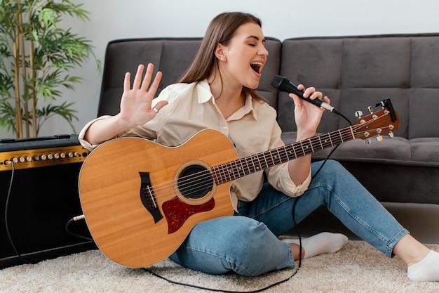 Smiley vrouwelijke muzikant akoestische gitaar spelen en zingen in de microfoon