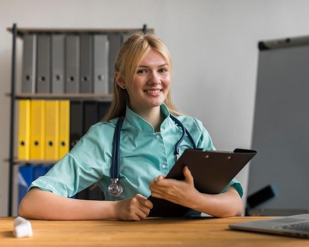 Smiley vrouwelijke verpleegster in het kantoor met kladblok en stethoscoop