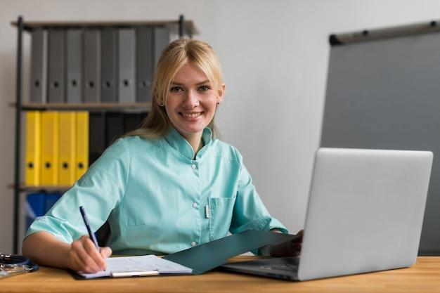 Smiley vrouwelijke verpleegster in het kantoor