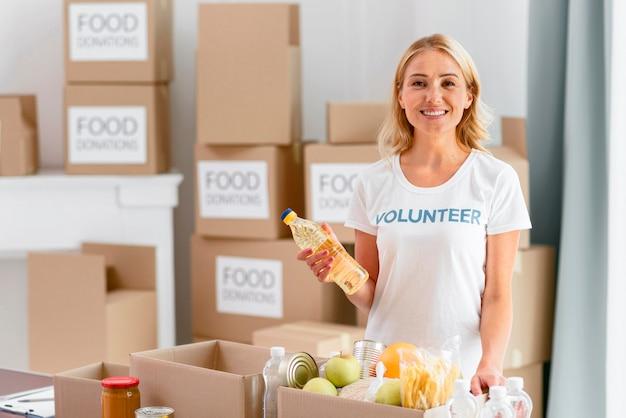 Smiley vrouwelijke vrijwilliger die doos met voedsel voorbereidt voor donatie