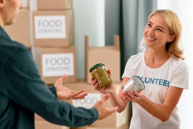 Smiley vrouwelijke vrijwilliger die persoon in nood helpt met voorzieningen