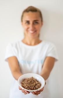 Smiley vrouwelijke vrijwilliger met kom met gedoneerd voedsel