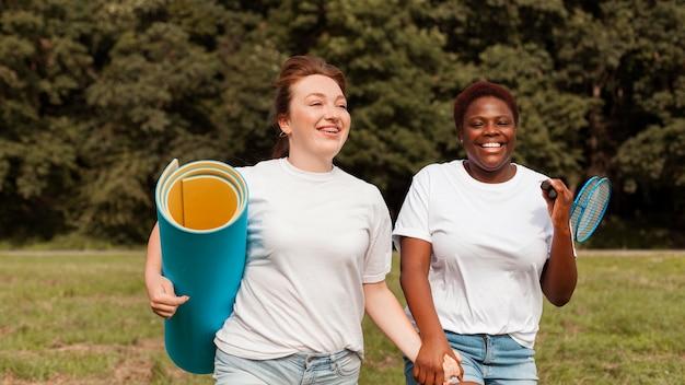 Smiley vrouwen hand in hand buitenshuis