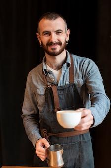 Smiley-werknemer die koffie maakt