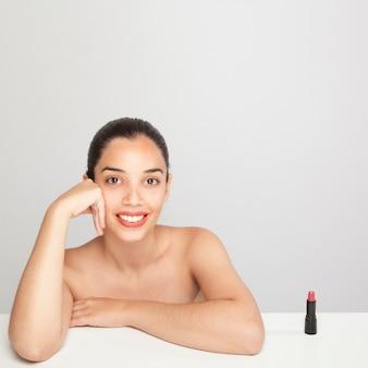 Smiley woaman poseren naast de lippenstift