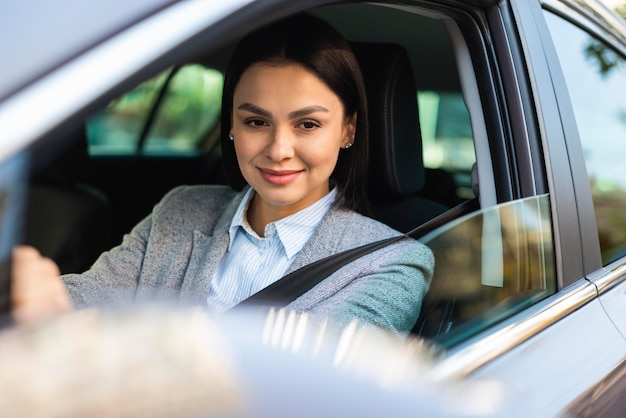 Smiley zakenvrouw haar auto rijden en in de zijspiegel kijken