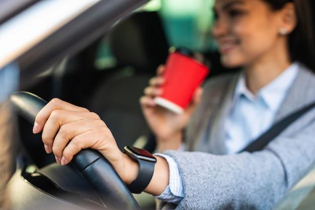 Smiley zakenvrouw met haar koffie tijdens het rijden