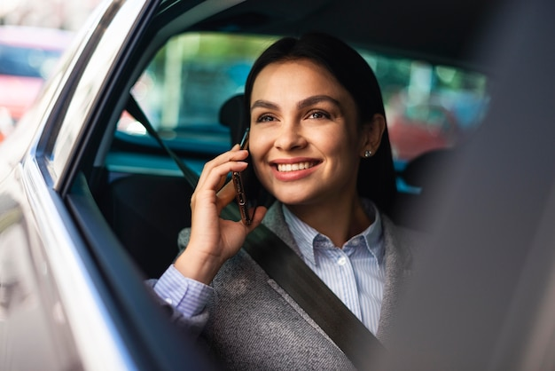 Smiley zakenvrouw praten aan de telefoon terwijl in de auto