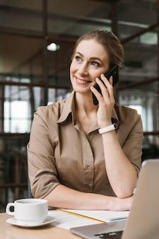 Smiley zakenvrouw praten aan de telefoon tijdens een vergadering