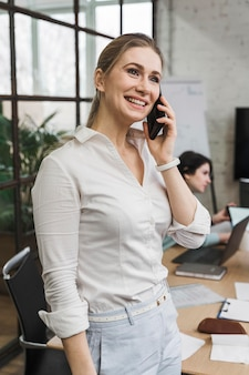 Smiley-zakenvrouw praten over smartphone tijdens een vergadering