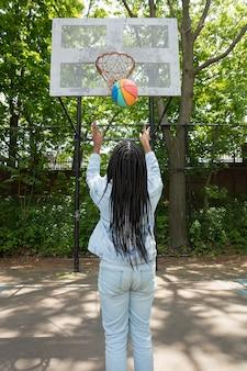 Smiley zwarte tiener die basketbal speelt