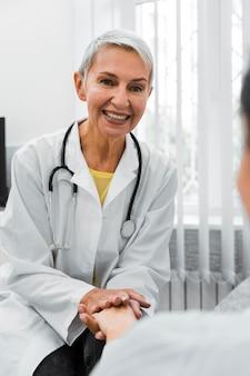 Smileyarts die de hand van een patiënt houdt