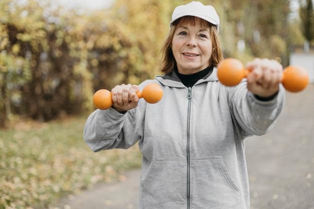 Smileybejaarde die met gewichten uitwerkt