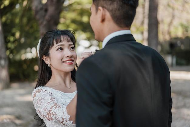 Smileybruid die de vlinderdas van de bruidegom schikken