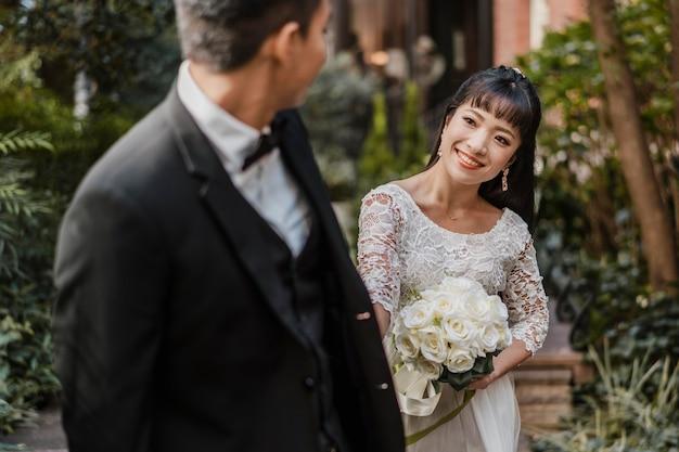 Smileybruid die met boeket de bruidegom bekijkt