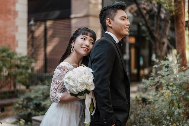Smileybruid die tegen de rug van de bruidegom leunt