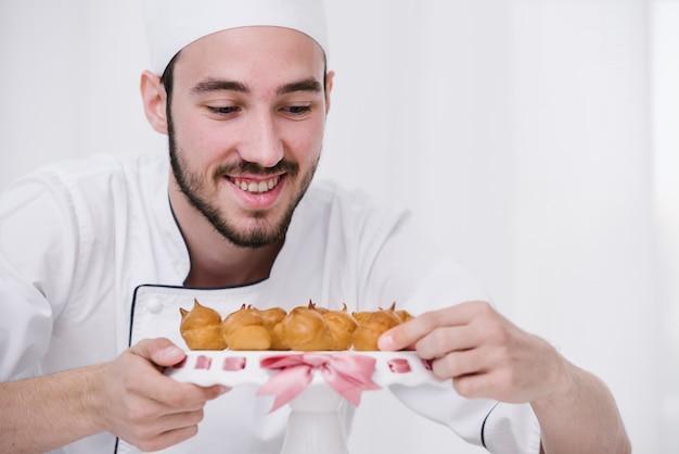Smileychef-kok die gevlamd schuimgebakje op een plaat voorstellen