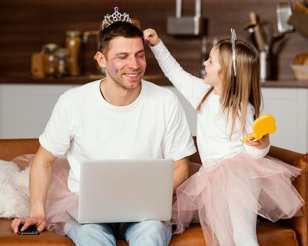Smileydochter die met vader speelt terwijl hij aan laptop werkt