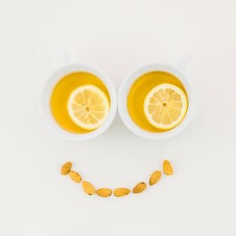 Smileygezicht met de kop van de citroenthee en amandelen wordt op witte achtergrond worden geïsoleerd gemaakt die