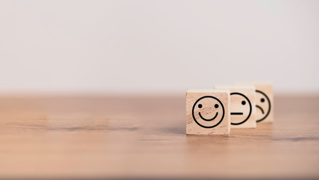 Smileygezicht voor normaal en verdrietig gezicht dat het scherm op een houten kubusblok afdrukt