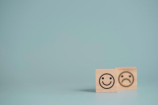 Smileygezicht voor verdrietig gezicht dat het scherm op houten kubusblok afdrukt, emotieselectie voor klanttevredenheid en evaluatieconcept.