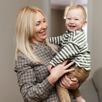Smileygrootmoeder die haar kleinzoon thuis houdt