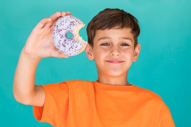 Smileyjongen die een verglaasde doughnut houden
