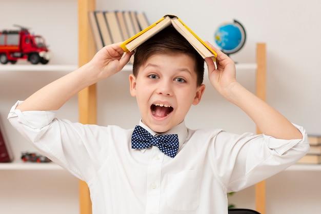 Smileyjongen met boek op zijn hoofd
