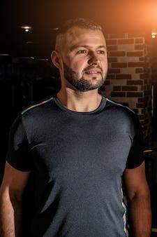 Smileykerel in zwart t-shirt, portret. portret van knappe alleenstaande bebaarde jonge man met ernstige uitdrukking dragen.