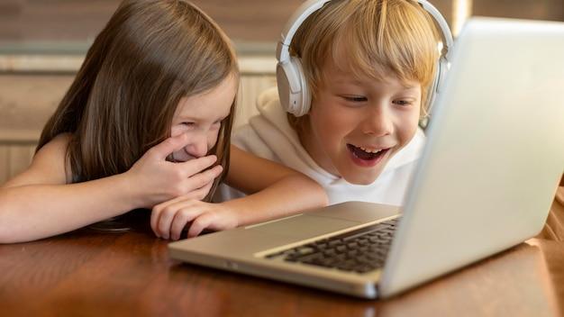 Smileykinderen die laptop en hoofdtelefoons samen gebruiken