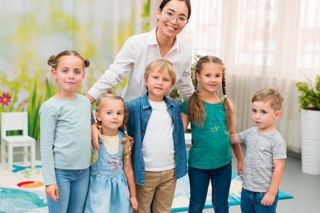 Smileyleraar die haar studenten vasthoudt op de kleuterschool