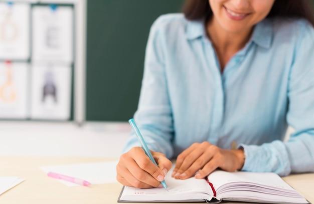 Smileyleraar die in haar notitieboekje schrijft