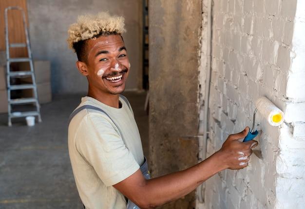 Smileyman die de muren van zijn nieuwe huis schildert