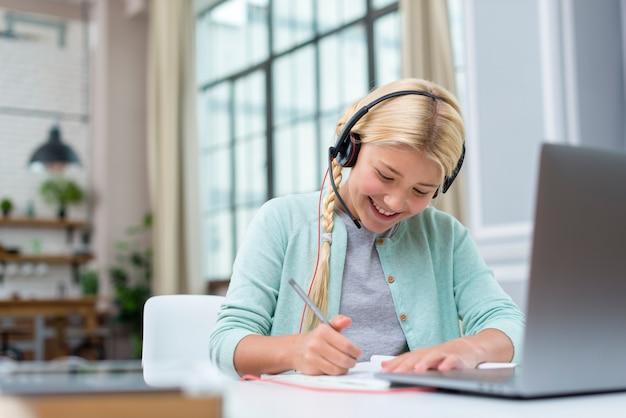 Smileymeisje die nota's van online cursus nemen