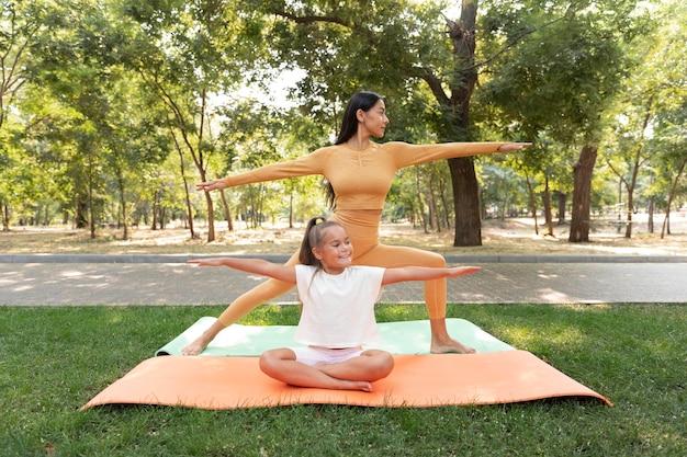 Smileymeisje en vrouw die yoga volledig schot doen