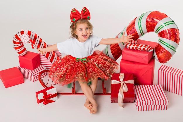 Smileymeisje omringd door kerstelementen