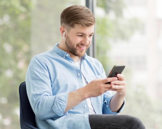 Smileymens met airpods die telefoon met behulp van