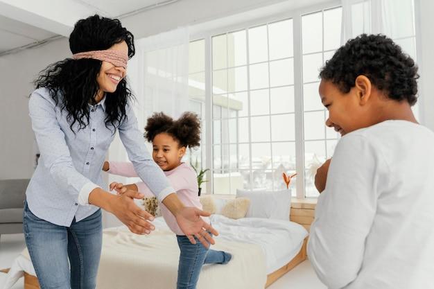 Smileymoeder die met haar kinderen thuis speelt