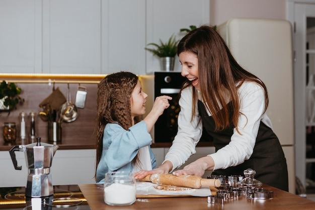 Smileymoeder en dochter die samen in de keuken koken