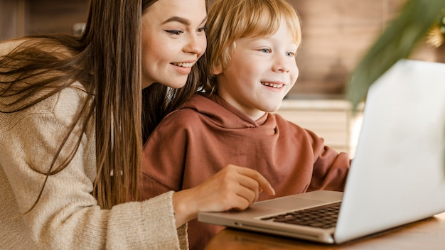 Smileymoeder en kind die laptop samen met behulp van