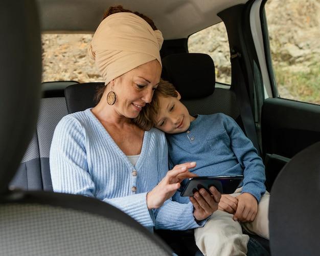 Smileymoeder en zoon in auto die mobiel met behulp van