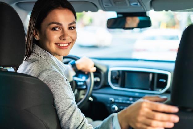 Smileyonderneemster die zich in de auto omdraait