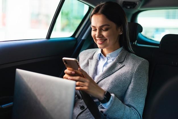 Smileyonderneemster in de auto met smartphone en laptop