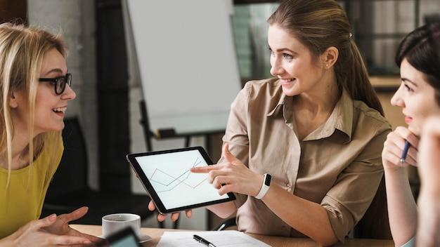 Smileyondernemers die tablet gebruiken tijdens een vergadering binnenshuis