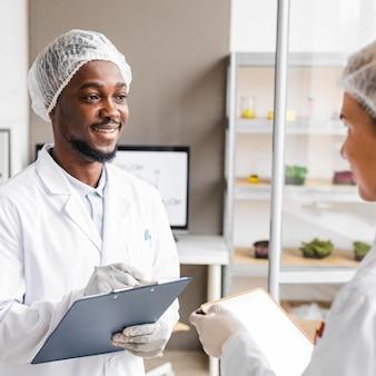 Smileyonderzoekers in het biotechnologielaboratorium met klembord en tablet