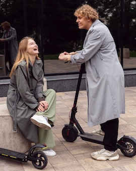 Smileypaar dat buiten met elektrische scooters praat
