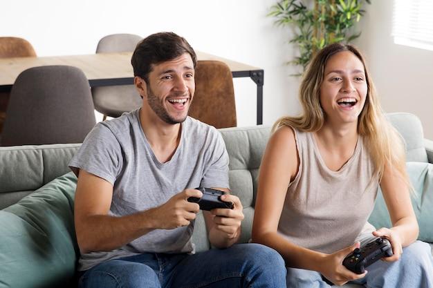 Smileypaar dat medium shot videogame speelt