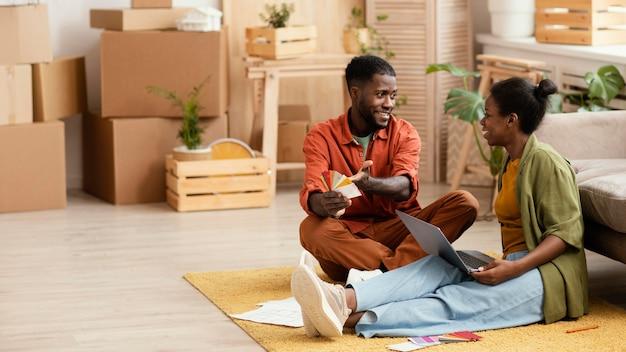Smileypaar dat plannen maakt voor het renoveren van huis met behulp van laptop en kleurenpalet